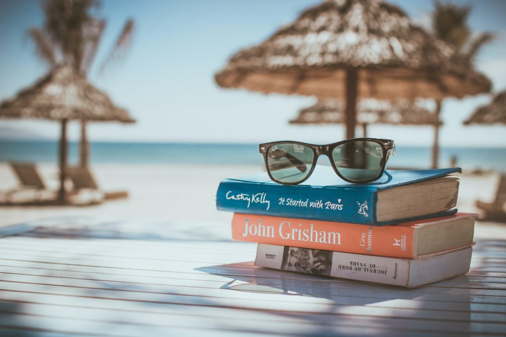 sunglasses on stack on books with beach  background.  Book Summer