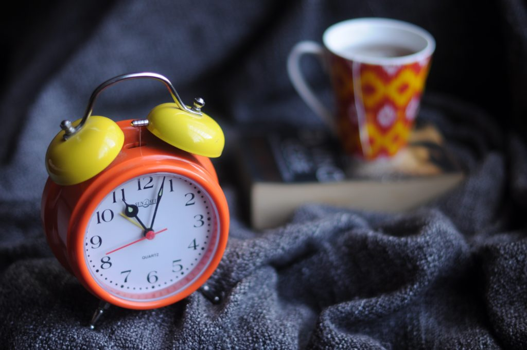 Clock in front of mug on top of book to motivate readers to make time